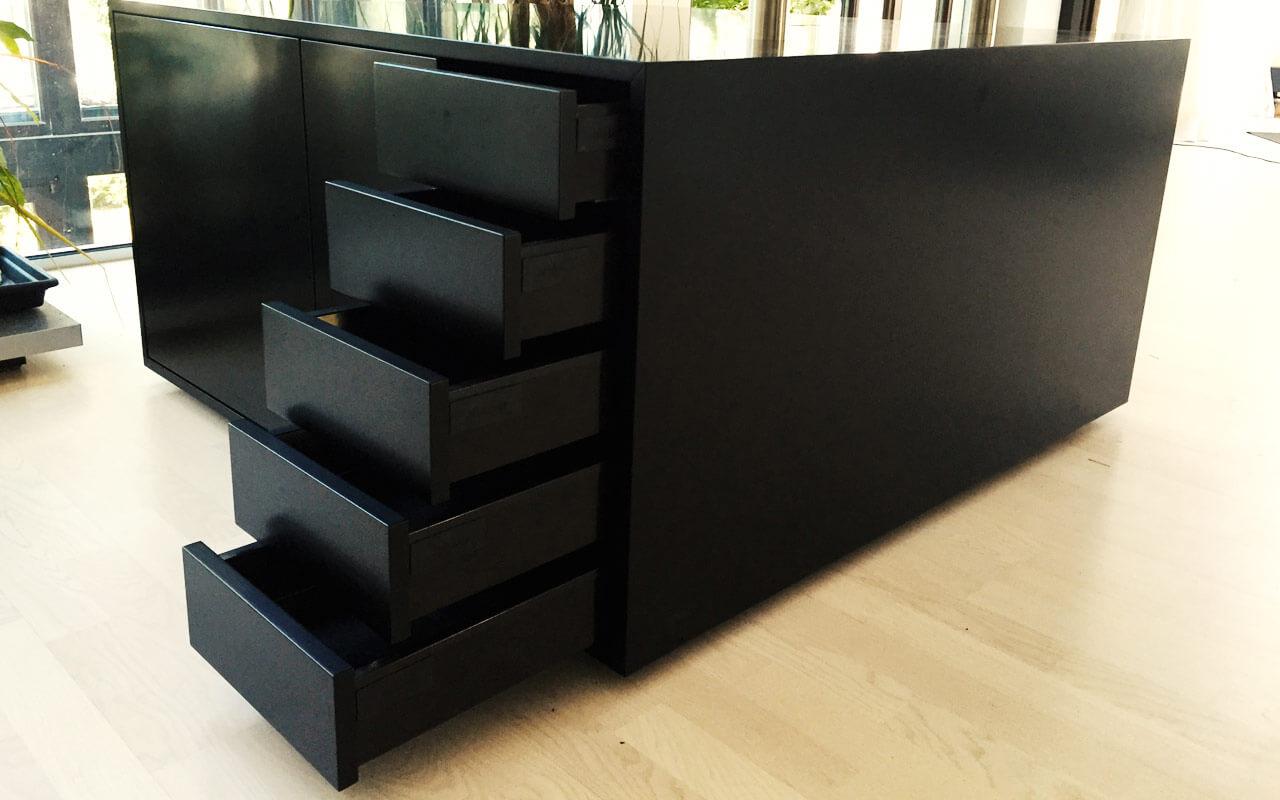 Schwarzer Schrank mit offenen Schubladen